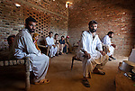 Refugees from the conflict in Buner, Pakistan, Mohammad Salim (centre)  with his ailing father Pardis Khan , six brothers ,wives and extended family are taking refuge in stables in the village of Bakar near Swabi. Numbering in the 70's they are sleeping up to 10 in a room after  the family  fled their home whilst the Pakistan Army attack Taliban insurgents across the Swat Valley.