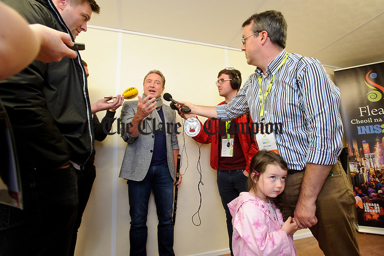Little Julie Ann Cooke hasn't the same interest in Michael Flatley as her Dad, RTE reporter John Cooke and the assembled media, as the world renowned dancer is interviewed before officially opening of the All-Ireland Fleadh 2017 in Ennis. Photograph by John Kelly.