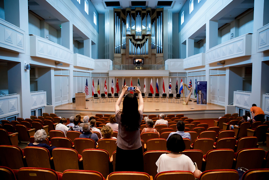 An audience member snaps a cell phone photo of Auer Hall before the opening ceremony of the 11th USA International Harp Competition at Indiana University in Bloomington, Indiana on Wednesday, July 3, 2019. (Photo by James Brosher)