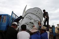 Local Tibetans attempt to move the head of a statue at Qinghai Lake. Qinghai Lake, China's largest inland body of water lies at over 3000m on the Qinghai-Tibetan Plateau. The lake has been shrinking in recent decades, as a result of increased water-usage for local agriculture. Qinghai Province. China. 2010