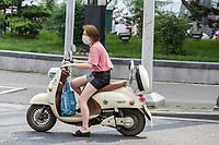 Suzhou, Jiangsu, China.  Young Chinese Woman with Breathing Mask on a Motorbike.