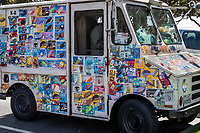 Colorful stickers, advertising ice cold treats, cover every open surface of an ice cream truck parked near the playgroud of a public park.