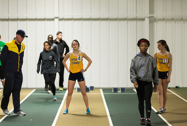 January 25, 2014. Winston Salem, North Carolina.<br /> Kayla Montgomery, center, warms up before running in the 1600m at the 2014 David Oliver Classic. Her coach, Patrick Cromwell, is at left.<br />  3 and a half years ago, during an examination after sustaining tailbone and head injuries from a fall during a soccer game, Kayla Montgomery, now 18, was diagnosed with multiple sclerosis. Montgomery, then a decent runner, refused to be limited by her diagnosis, and after years of training has become one of the best high school runners in the country.