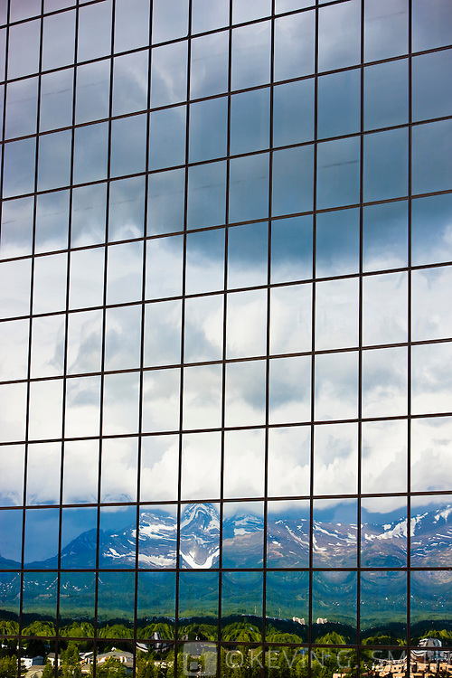 The Chugach Mountains reflected in windows of the Atwood Tower, summer, Anchorage, Southcentral Alaska, USA.