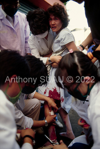"""Seoul, South Korea.June 26, 1987..A young woman is injured by a tear gas grenade as many civilians were caught up in the political street riots that swept Seoul...After two decades of building an economic miracle, in the summer of 1987 tens of thousands of frustrated South Korean students took to the streets demanding democratic reform. """"People Power"""" Korean-style saw Koreans from all social spectrums join in the protests...With the Olympics to be held in South Korea in 1988, President Chun Doo Hwan decided on no political reforms and to choose the ruling party chairman, Roh Tae Woo, as his heir. The protests multiplied and after 3 weeks Chun conceded releasing oppositionist Kim Dae Jung from his 55th house arrest and shaking hands with opposition leader Kim Young Sam. Days later he endorsed presidential elections and an amnesty for nearly 3,000 political prisoners. It marked the first initiative of democratic reform in South Korea and the people had their victory."""