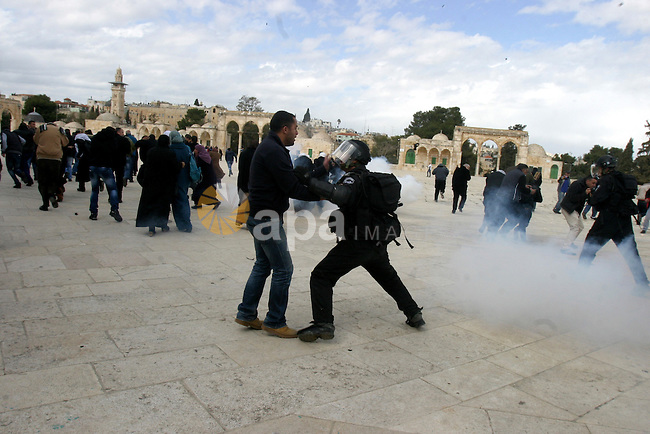 Israeli riot police clashing with Palestinians as the police hurl stun grenades and rocks are seen flying on the plaza next to the Dome of the Rockduring clashes with Palestinian protesters on the compound known to Muslims as the Noble Sanctuary and to Jews as the Temple Mount in Jerusalem's Old City February 24, 2012. Israeli policemen stormed the compound on Friday following prayers, using stun grenades to disperse stone-throwing Palestinian protesters, some of whom then retreated into al-Aqsa mosque. Israeli police spokesperson said 11 policemen were lightly injured from stones and 4 protesters were arrested. Photo by Mahfouz Abu Turk