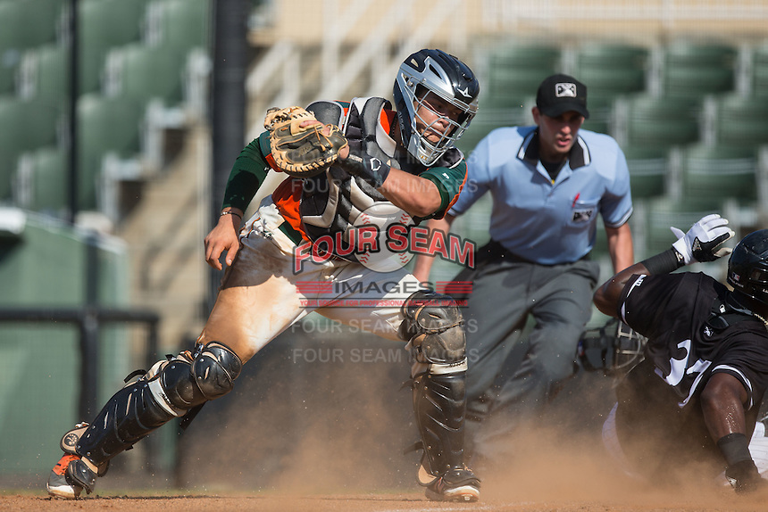 Micker Aldofo (37) of the Kannapolis Intimidators slides across home plate ahead of the tag attempt by Greensboro Grasshoppers catcher Roy Morales (17) at Intimidators Stadium on July 17, 2016 in Greensboro, North Carolina.  The Intimidators defeated the Grasshoppers 3-2 in game one of a double-header.  (Brian Westerholt/Four Seam Images)