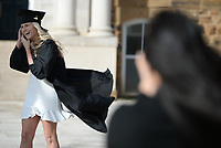 Kaylea Stevens (left), a University of Arkansas senior from Rock Wall, Texas, laughs Thursday, Nov. 19, 2020, as Sonam Biggs, owner of Sonam Biggs Photography in Fayetteville, takes her photograph in her cap and gown on the university campus in Fayetteville. Stevens is set to graduate in December and does not plan return to in-person instruction on campus after the Thanksgiving break because of the pandemic. Visit nwaonline.com/201120Daily/ for today's photo gallery. <br /> (NWA Democrat-Gazette/Andy Shupe)