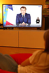 Coronavirus Pandemic - French President Emmanuel Macron address  in Paris, France on March 31, 2021. A girl watch a TV Screen showing French President Emmanuel Macron address. In France a new Confinement due to the various Variant ot the Novel Coronavirus with school closing will be in place at least for April 2021. Europe try again to slow down the spread of Covid-19 pandemic.