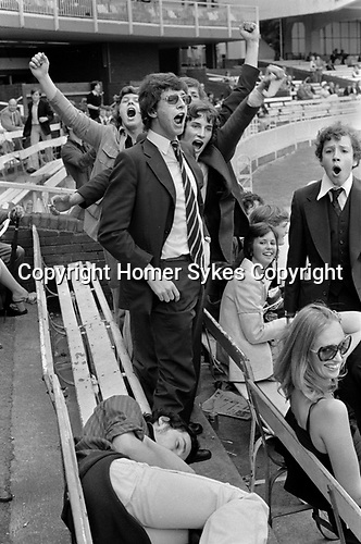 St Johns Wood, London. 1975<br /> At the annual Eton v Harrow cricket match,  a group of excited young Harrovians cheer their own success  and jeer  their  vanquished opponents, while one of their number sleeps off an afternoons excess.