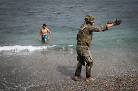 CEUTA, SPAIN ‐ MAY 19: A Spanish soldier negotiates with a migrant on the Tarajal beach to get him out of the water after having crossed the border between Morocco and Spain swimming on May 19, 2021 in Ceuta, Spain.  After a diplomatic conflict between Spain and Morocco, thousands of migrants who have taken advantage of the little Moroccan police activity on the border to cross it mainly by swimming, which has caused a migration crisis with the entry of more than 8000 migrants from the African country. (Photo by Joan Amengual/VIEWpress )