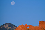 A full moon sits high above the Kissing Camels formation in the Garden of the Gods city park, Colorado Springs, CO
