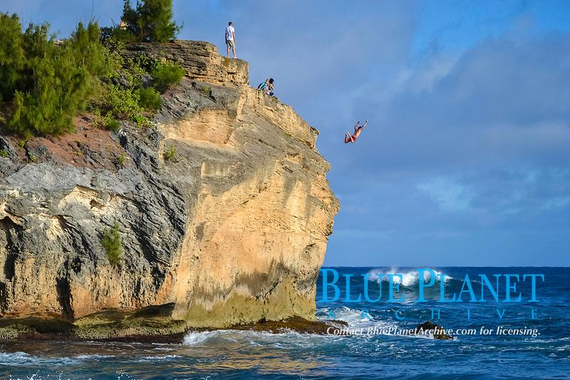 Man jumps from the top of a rock in Shipwreck Beach, Poipu, Kauai, Hawaii, USA