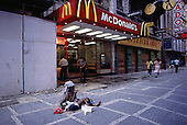Sao Paulo, Brazil. Woman with a small child on her lap begging outside McDonald's.