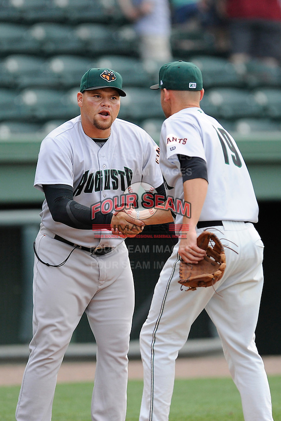Manager Nestor Rojas, left, congratulates second baseman Hunter Cole (19) of the Augusta GreenJackets after a game against the Greenville Drive on Sunday, April 12, 2015, at Fluor Field at the West End in Greenville, South Carolina. Augusta won, 2-1. (Tom Priddy/Four Seam Images)