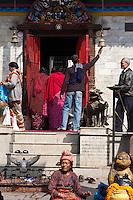 Kathmandu, Nepal.  Nepali Worshippers Ring a Bell at a Temple's Entrance to Drive Away Evil Spirits.  Mahendreshwar Temple, Durbar Square.