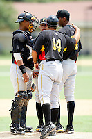 July 13, 2009:  Manager Tom Prince of the GCL Pirates talks with pitcher Rinku Singh, Catcher Jairo Marquez, and Shortstop Benjamin Gonzalez during a game at Tiger Town in Lakeland, FL.  The GCL Pirates are the Gulf Coast Rookie League affiliate of the Pittsburgh Pirates.  Photo By Mike Janes/Four Seam Images
