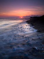 A vivid sunset casts its light on waves landing on the black sand of Honokohau Beach, Big Island.