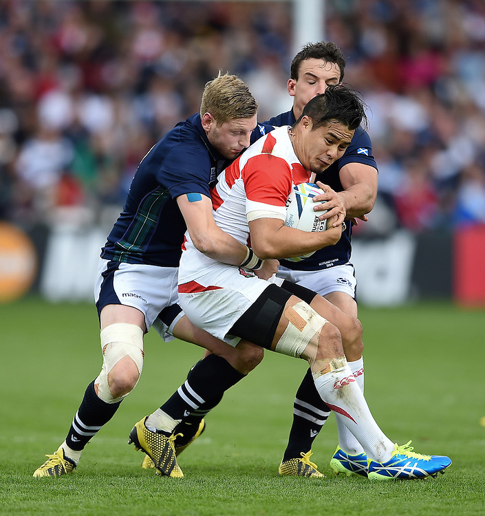 Yu Tamura of Japan is double-tackled. Rugby World Cup Pool B match between Scotland and Japan on September 23, 2015 at Kingsholm Stadium in Gloucester, England. Photo by: Patrick Khachfe / Stewart Communications