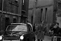 """Tournage du film """"La Bourse ou la Vie"""" de Jean Pierre Mocky, dans le quartier de St Sernin, Tououse, France, novembre 1965<br /> <br /> 2 novembre 1965. Plan d'ensemble de face de l'acteur Jean Poiret portant le béret, marchant à côté d'une voiture, avec autour de lui quelques figurants et des passants, lors du tournage <br /> <br /> PHOTO:  Fonds André Cros,"""