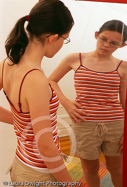 Teenage girl 12 years old looking at self in distorted mirror vertical