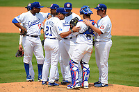 Chattanooga Lookouts pitching coach Hector Berrios #21 talks with pitcher Hector Nelo #45, catcher Jan Vazquez #6, first baseman J.T. Wise #31, as Omar Luna #12, Miguel Rojas #13, and Rafael Ynoa #5 listen in during a game against the Birmingham Barons on April 17, 2013 at AT&T Field in Chattanooga, Tennessee.  Chattanooga defeated Birmingham 5-4.  (Mike Janes/Four Seam Images)