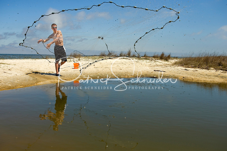 A teenage cases a fishing net on Dauphin Island, Alabama, a barrier island located three miles south of the mouth of Mobile Bay in the Gulf of Mexico. This island, which is approximately 14 miles long and less than two miles wide, appears to have fully recovered from the impact of Hurricane Katrina (2005) and the BP Deepwater Horizon Oil Spill in 2010. Both events greatly reduced tourism income (fewer people came to the island) and local business owners say many establishments went out of business. Today they say they're looking forward to a rebounding tourism business.