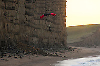 BNPS.co.uk (01202 558833)<br /> Pic: Graham Hunt/BNPS<br /> <br /> Weekend daredevil<br /> <br /> A daredevil base jumper leaps from the of the vertical cliffs made famous by Broadchurch and on to the beach at West Bay in Dorset at sunrise.