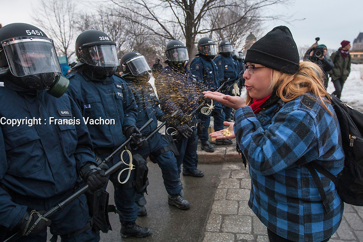 A your woman blow glitters at an anti-riot policeman during a protest against austerity organized by the ASSE student group in Quebec city Thursday March 26, 2015.<br /> <br /> PHOTO :  Francis Vachon - Agence Quebec Presse