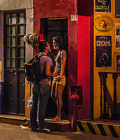 Fine Art Print. Puerto, Vallarta, Mexico. Night photography, street scene of two young lovers meeting each other under the evening street lights.