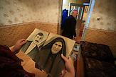 Emil Gamidov, 70, geht aus dem Zimmer in seinem Haus in Kant, Kirgisistan. Seine  Frau hält die Porträts von ihren Eltern, die aus Atskuri Dorf deportiert wurden, in den Händen . Gamidov war erst 3, als er aus Georgien nach Kasachstan deportiert wurde.  Jahre später ging  er für sein Studium nach  Bischkek. Er lebt immer noch in Kirgisistan. / Emil Gamidov, 70, walks out of the room in his house in Kant, Kyrgyzstan as his wife holds the portraits of her parents, who were deported from Atskuri village. Gamidov was only 3 when he was deported from Georgia to Kazakhstan. Years later, he moved to Bishkek for his graduate studies. He still lives in Kyrgyzstan.