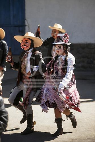 Paucartambo, Peru. Masked couple dancers carrying bottles of beer at the Fiesta de la Virgen del Carmen.