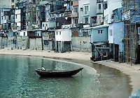A single boat is anchored near the shore by a section of dilapidated houses in Hong Kong, housing. Hong Kong, China.