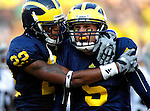 Michigan wide receiver Darryl Stonum (22) celebrates with quarterback Tate Forcier (5) after Forcier scored a touchdown in the second half of an NCAA college football game with Notre Dame, Saturday, Sept. 12, 2009, in Ann Arbor. Michigan upset No. 18 Notre Dame 38-34. (AP Photo/Tony Ding)