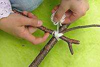 Kinder weben ein Blumenbild, Mädchen legt einen Rahmen aus Ästen und bindet ihn an den Ecken zusammen