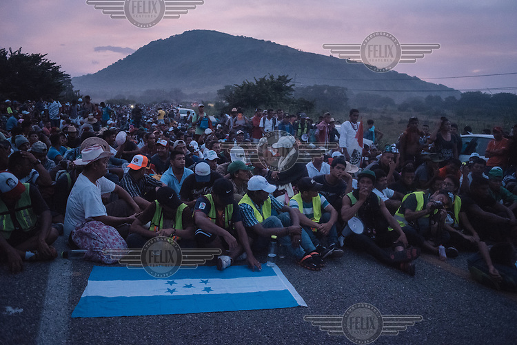 A caravan of Central American migrants dispaly a Honduran flag as they sit on a highway after being blocked from getting to Tapanatepec by a wall of Mexican police in riot gear, outside Arriaga.
