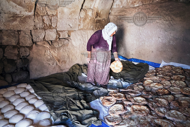 A woman puts freshly baked flat breads on the ground in a stone room where the tepid air will keep it soft after it cools down.