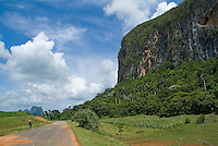 Man walking on a rural road alongside the Mogotes in the Vinales Valley, Cuba.