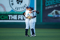 Everett AquaSox outfielders Charlie McConnell (19), Jansiel Rivera (36), and Josh Stowers (25) hug after the last game of the Northwest League regular season against the Tri-City Dust Devils at Everett Memorial Stadium on September 3, 2018 in Everett, Washington. The Everett AquaSox defeated the Tri-City Dust Devils by a score of 8-3. (Zachary Lucy/Four Seam Images)
