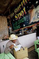 Iles Bahamas / New Providence et Paradise Island / Nassau: Dans un petit restaurant de rue du Marché de Potter's Cay sous le pont de Paradise Island - une cliente mange une salade de conque Conch Salad spécialité emblématique de la cuisine bahamienne // Bahamas / New Providence and Paradise Island / Nassau Islands: In a small street restaurant in Potter's Cay Market under the Paradise Island Bridge - a customer is eating a conch salad Conch Salad specialty emblematic of the Bahamian cuisine