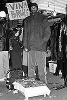 """Milano, quartiere Sant'Ambrogio. Fiera degli Oh Bej! Oh Bej!, tradizionale mercatino del periodo natalizio milanese. Un ragazzo africano vende cd """"taroccati"""" --- Milan, Sant'Ambrogio district. Oh Bej! Oh Bej!, traditional Milanese Christmas fair. An African boy selling fake cds"""
