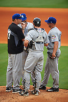 Biloxi Shuckers pitching coach Chris Hook (37) talks with pitcher Jacob Barnes (27) as catcher Parker Berberet (21) and Yadiel Rivera (13) listen in during the second game of a double header against the Pensacola Blue Wahoos on April 26, 2015 at Pensacola Bayfront Stadium in Pensacola, Florida.  Pensacola defeated Biloxi 2-1.  (Mike Janes/Four Seam Images)