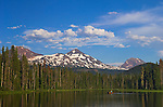 Scott Lake and the Three Sisters (volcanic moutain peaks) with man paddling canoe; Cascade Mountains, Oregon..#0607237