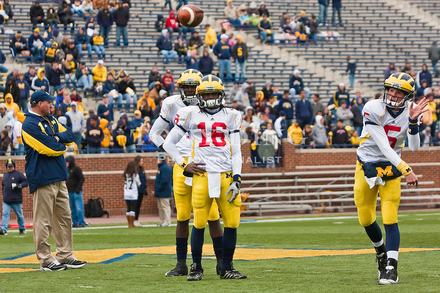 Michigan quarterback Denard Robinson (16) watches quarterback Tate Forcier (5) throws a pass during warmups before the Wolverines' spring football game, Saturday, April 17, 2010, in Ann Arbor, Mich. (AP Photo/Tony Ding)