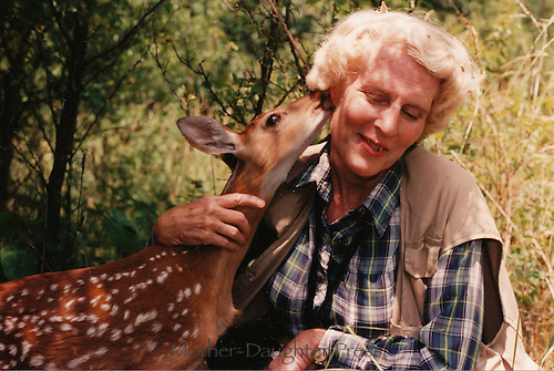 Gay McDonnell Bumgarner, Photographer, being licked by an orphan fawn after feeding