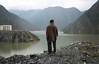 A Tibetan man looks out onto a reservoir which lies behind the Maoergai Dam. Three villages were flooded when the dam was created leading to the relocation of hundreds of local residents.