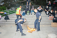 """Northeastern University police extinguish an American flag burning on the sidewalk during the """"Unite Against Racist Police Terror! Boston Speakout and March"""" demonstration in Boston, Massachusetts, on Sun., June 7, 2020. The march was peaceful and organizers quickly asked people not to do things like burn flags. Northeastern University Police quickly extinguished the flames. The march started outside Boston's City Hall and ended near the Boston Police Department Headquarters at Ruggles station. The march is part of ongoing nationwide demonstrations against police brutality in the weeks after George Floyd was killed by police in Minneapolis on May 25, 2020. Police officers knelt on George Floyd's neck for 8 minutes and 46 seconds."""