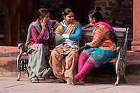 Fatehpur Sikri, Uttar Pradesh, India.  Indian Women Talking, Seated on Bench.