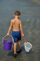 A young boy tried his luck catching fish at the ocean beach.