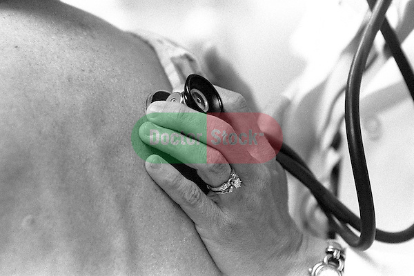 Close-up of doctor's hand holding stethoscope on female patient's back; listening to heartbeat